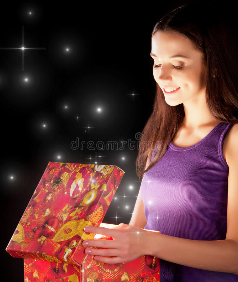 The girl opens the gift. For the holiday stock photos