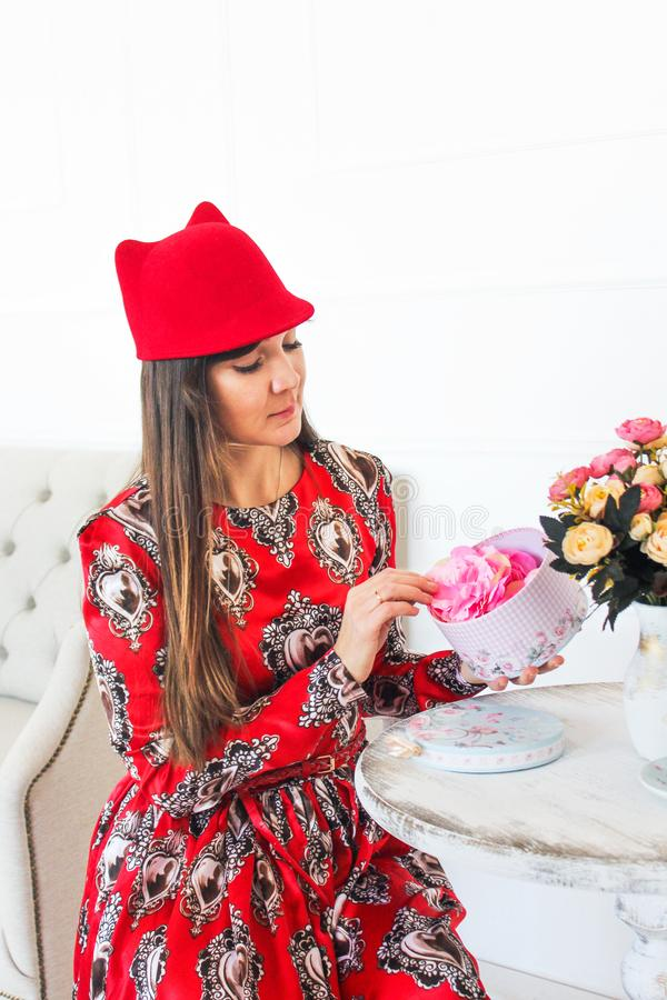 The girl opens the gift. The girl in the red dress and hat sits at a table and opens the gift stock image