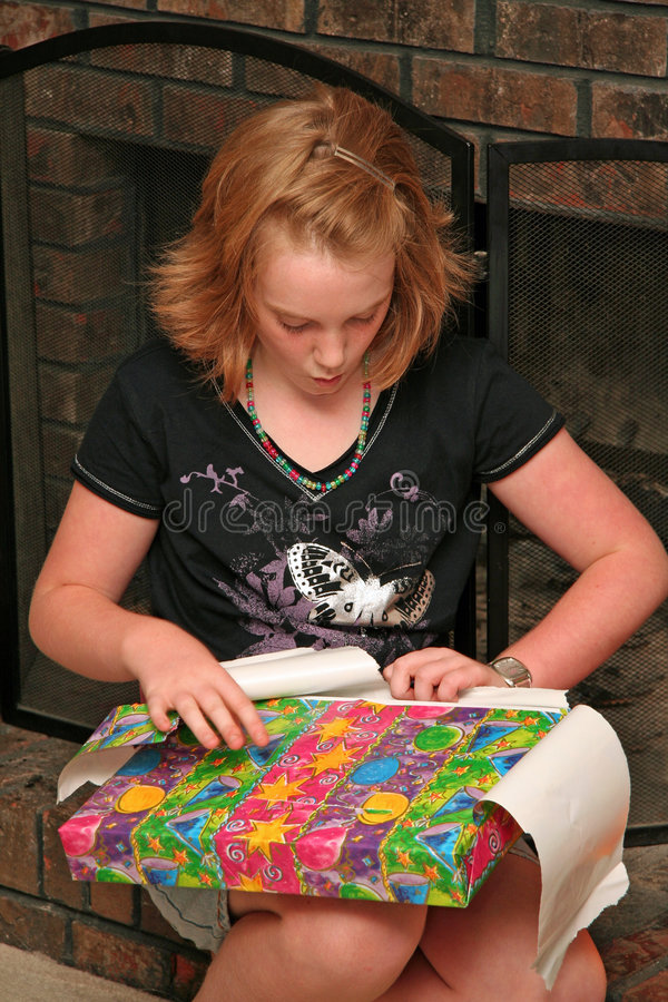Girl opens present. A young tween girl opens a brightly colored birthday present stock photo