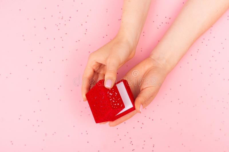 Girl opens a red velvet gift box on a pink background royalty free stock photography