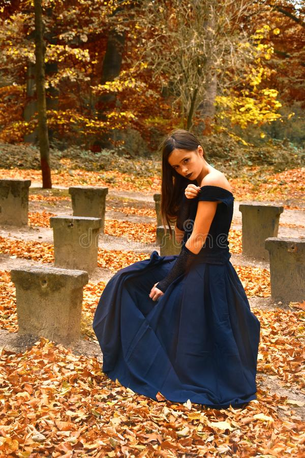 Girl in orange autumn forrest. Teenage girl with long brown hair and in black dress sitting alone in orange Fall forrest stock photos