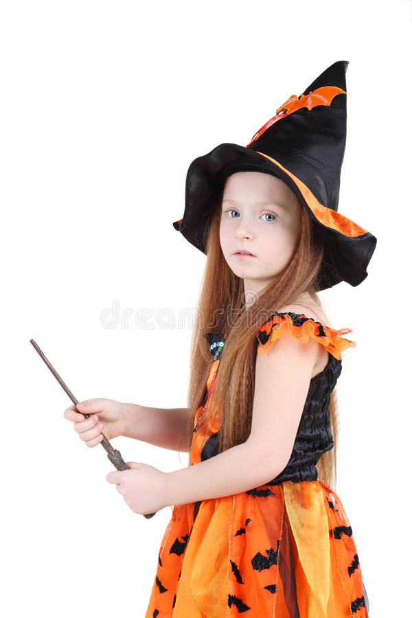 Girl in orange costume of witch for Halloween holds wand royalty free stock images