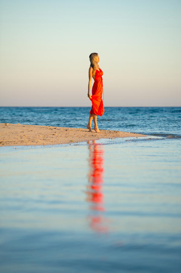 Girl in orange dress by seas edge. A beautiful girl in orange dress by seas edge at sunset stock image