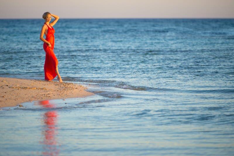 Girl in orange dress by seas edge 2