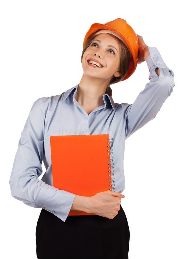 Girl in orange helmet looks up. Happy girl in orange helmet looks up royalty free stock photo