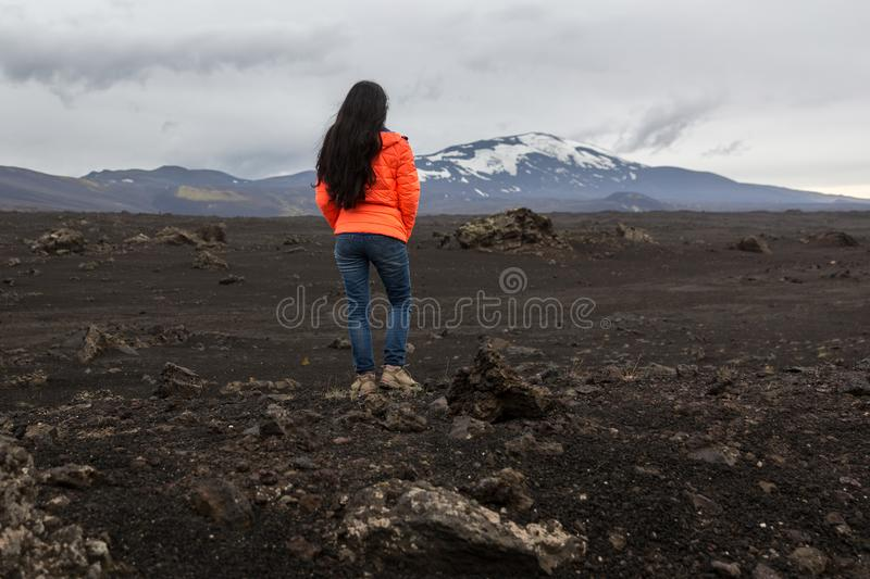 Girl in an orange jacket stands on a stone royalty free stock photos