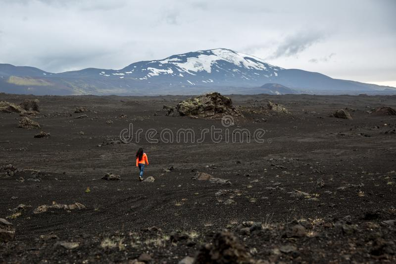A girl in an orange jacket walks through a burnt-out lava field royalty free stock photos