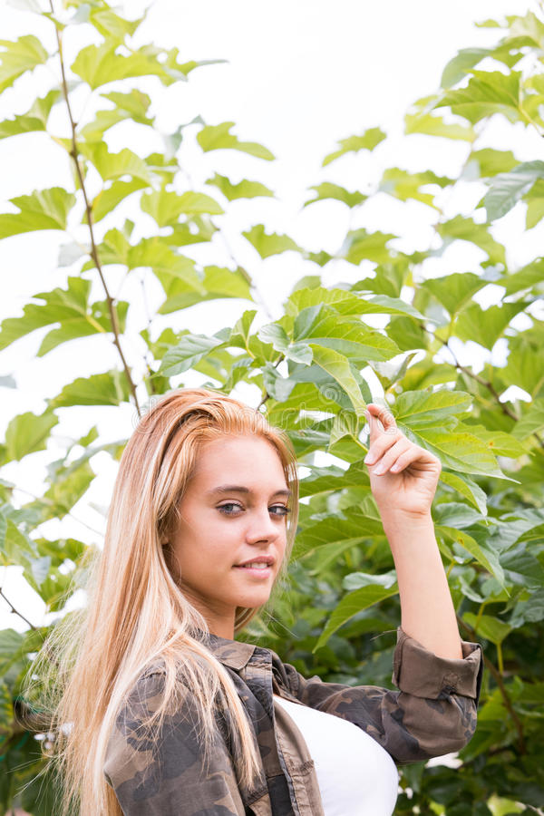 Girl outdoors touching a leaf. Blond beautiful girl loving nature outdoors as she touches a green leaf respecting its spirit royalty free stock photo