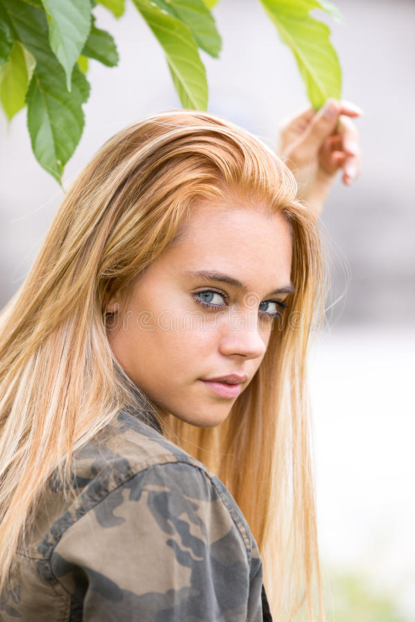Girl outdoors touching a leaf. Blond beautiful girl loving nature outdoors as she touches a green leaf respecting its spirit royalty free stock photography