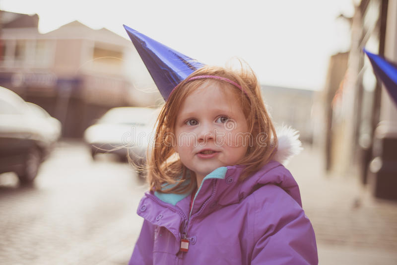 Girl (4) outdoors in winter coat and party hat. Young girl with ginger hair and blue/green eyes standing outside with a warm winter coat and a blue party hat stock photography