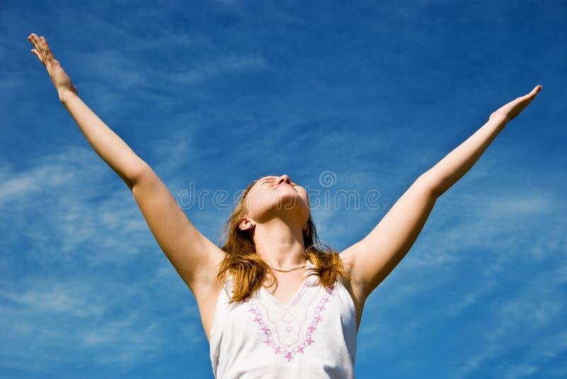 Girl over blue sky stock photography