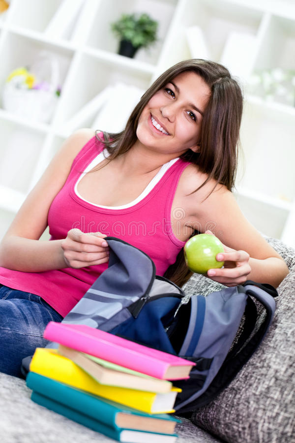 Girl packing books for school stock photography