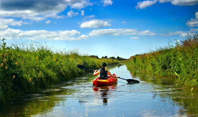 Girl with paddle and kayak royalty free stock photo