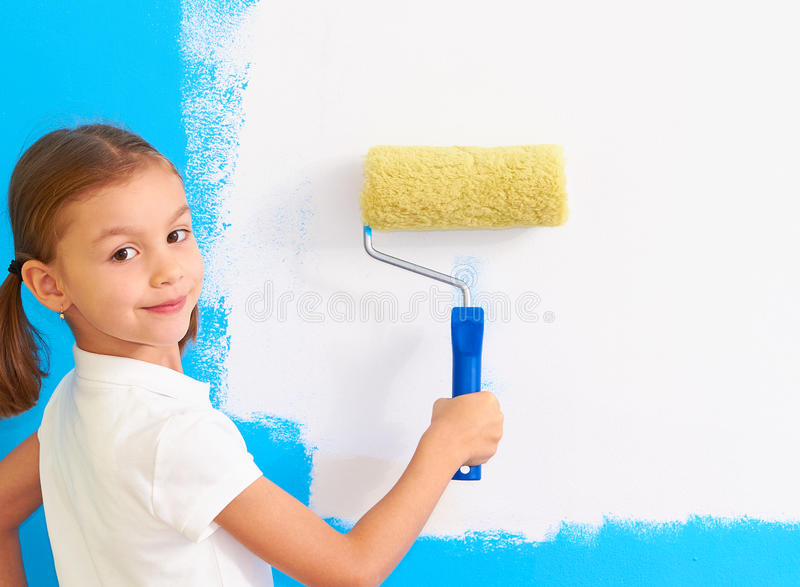 Girl with paint roller next to an wall stock images