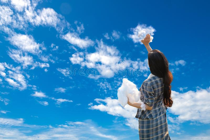 Girl Painted Beautiful Blue Sky with Her Clouds. Creative and Creation Surreal Concept Picture stock photography