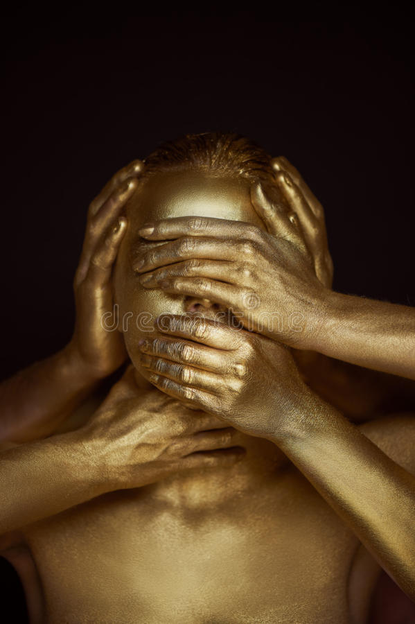 Girl painted gold. 6 hands on your face: see no evil, hear no evil, speak no evil. stock images
