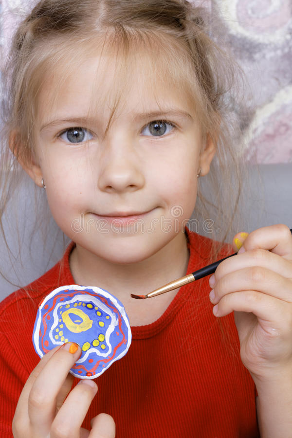 Girl with painted homemade clay cup. Focus on brush stock image