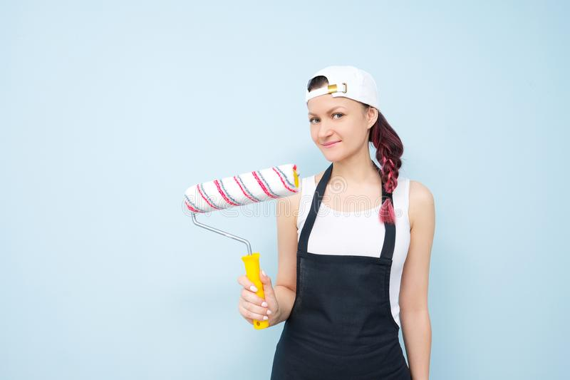 Girl painter, designer and worker paints a roller and brush the wall. stock images