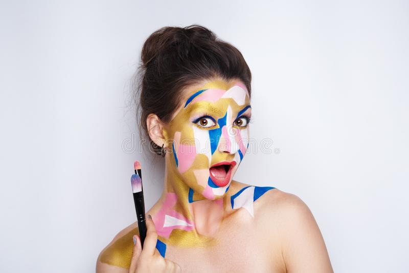 Woman artist make up. Girl painter holds black artist professional brush, all body Painted in gouache watercolor acrylic oil paints. Creative makeup new royalty free stock images