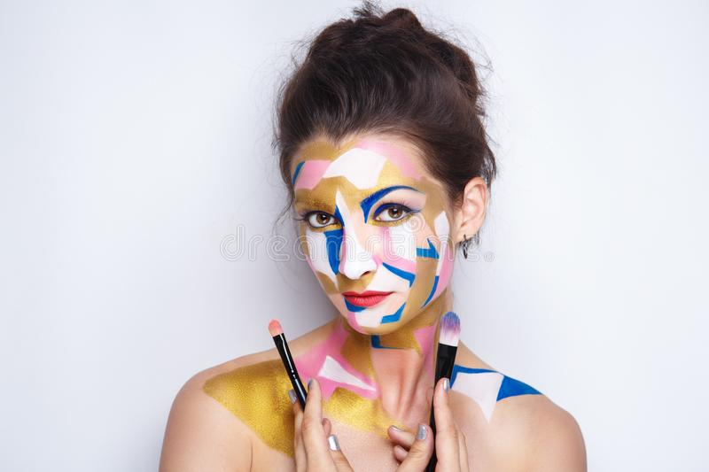 Woman artist make up. Girl painter holds black artist professional brush, all body Painted in gouache watercolor acrylic oil paints. Creative makeup new stock photos