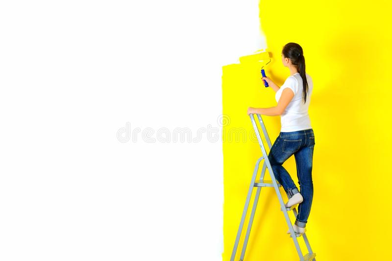 Girl painter paints a wall royalty free stock images