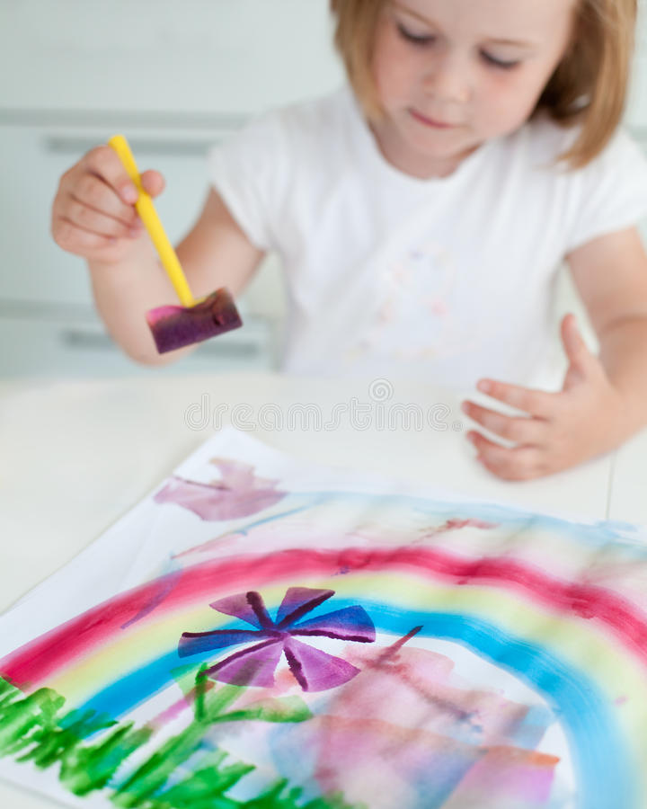 Girl painting. Young girl painting a flower and rainbow with watercolors royalty free stock image