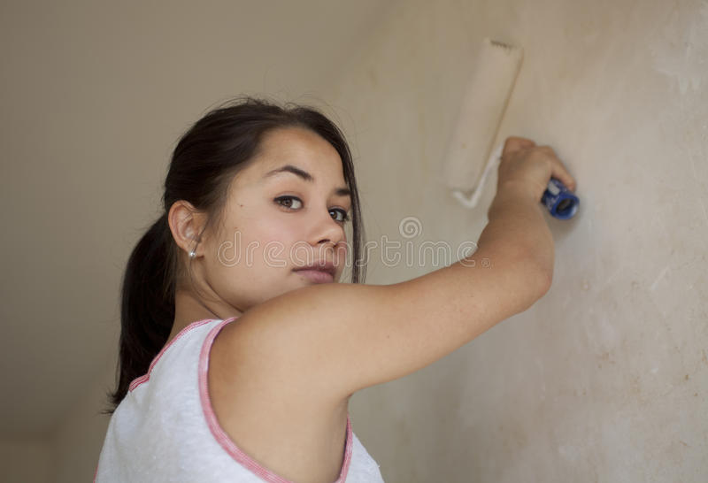 Girl painting apartment. Inside at day time stock photos