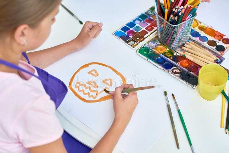 Girl Painting in Art Class for Halloween. High angle portrait of teenage girl painting pictures on Halloween enjoying art lesson in development school royalty free stock image