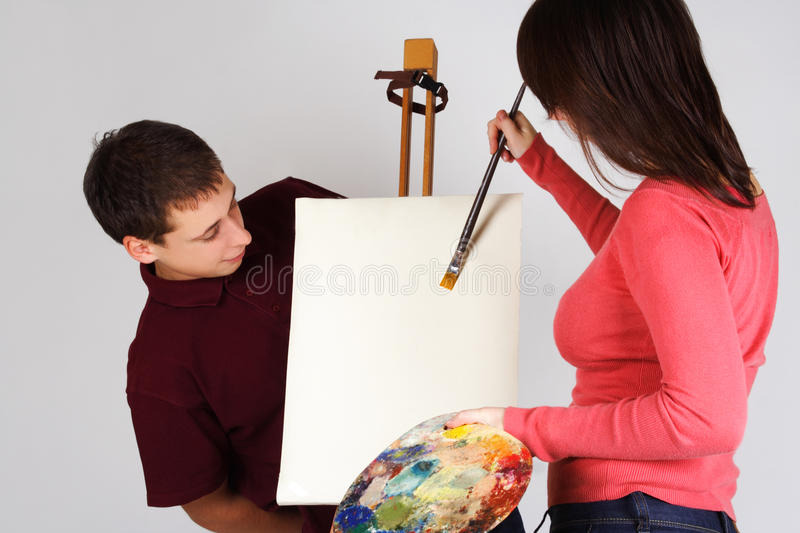 Girl painting on canvas easel, man looking royalty free stock photography
