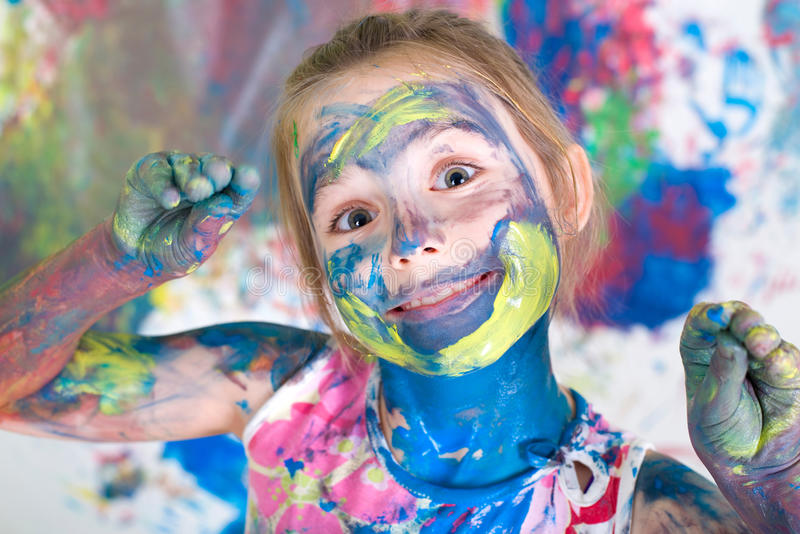 Girl painting with colors. On her face stock photos