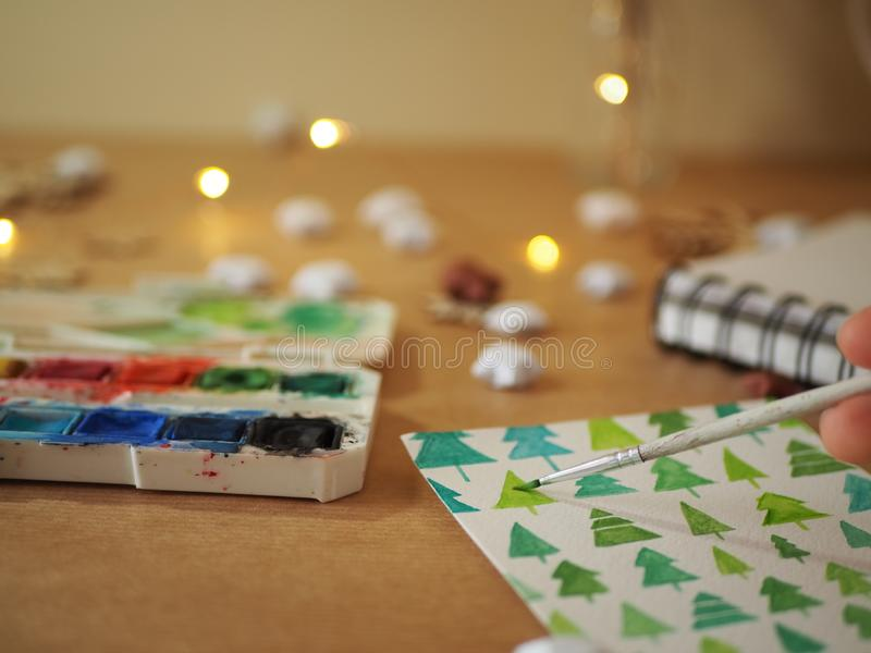 A girl painting green Christmas trees on a white sheet of paper with paints stock images