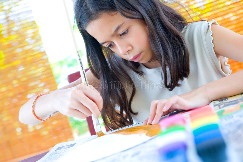 Girl painting a paper plate with poster paint. Young girl painting a paper plate with poster paint and wooden brush stock photos
