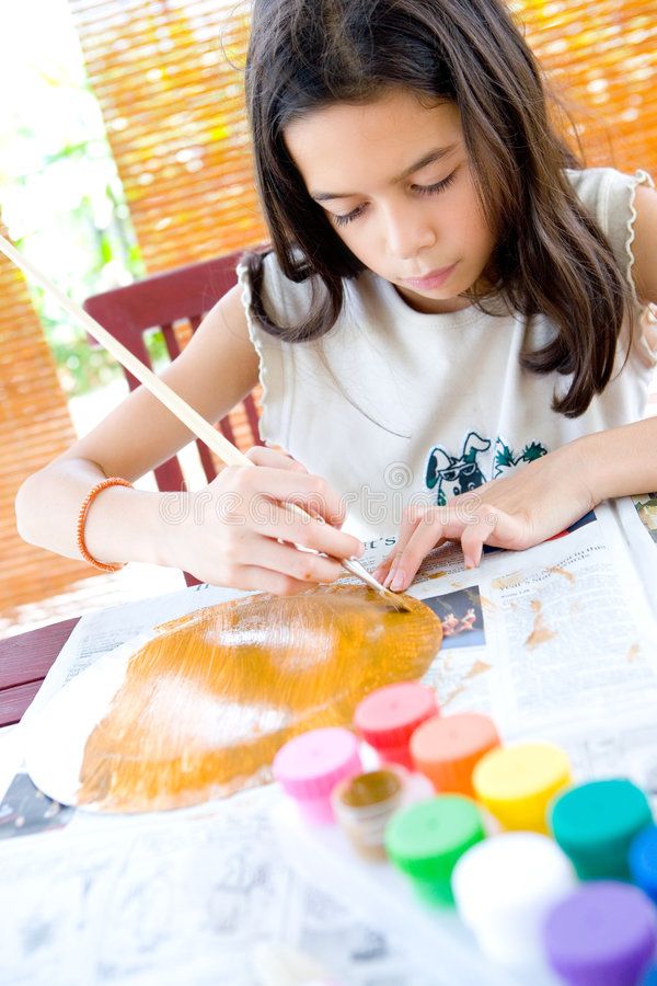 Girl painting a paper plate with poster paint. Young girl painting a paper plate with poster paint and wooden brush stock photography