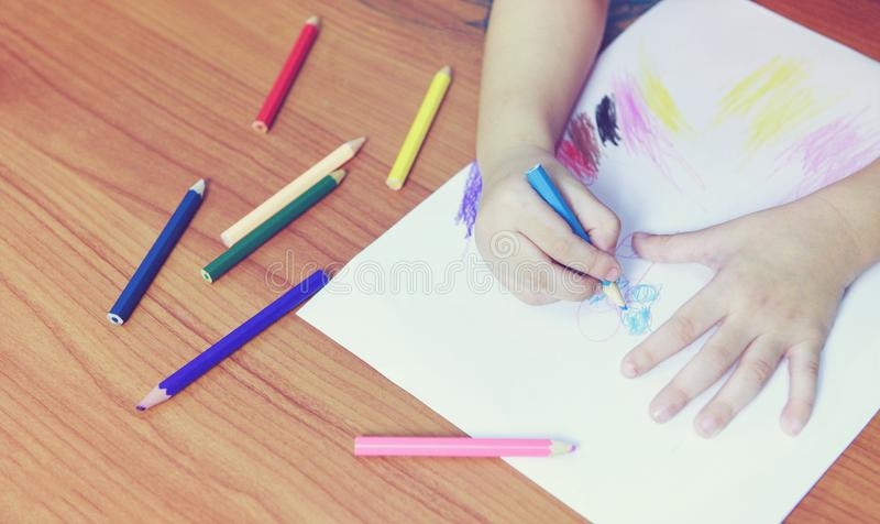 Girl painting on paper sheet with colour pencils on the wooden table at home - child kid doing drawing picture and colorful crayon royalty free stock image