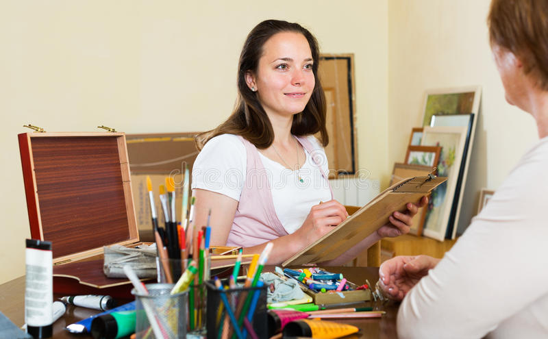 Girl painting portrait of mature woman. Girl painting portrait of mature women at workshop stock photos