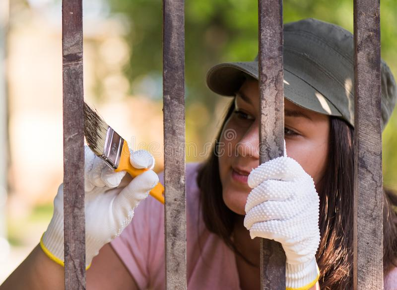 Girl is painting wooden fence with a brush royalty free stock photos