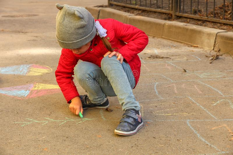 Girl paints crayons on the asphalt stock image