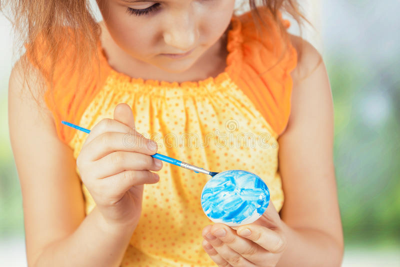 Girl paints Easter egg in blue color stock photo