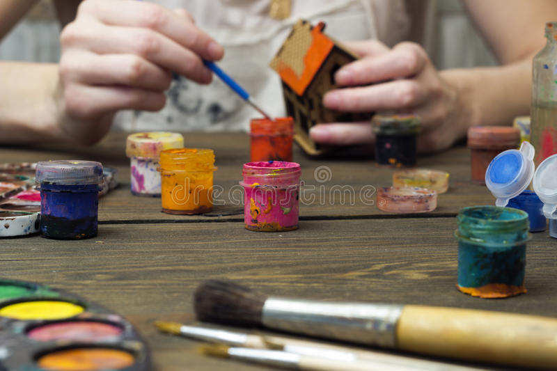 Girl paints house paints and brushes. On the table royalty free stock photography