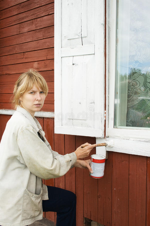 The girl paints a house window royalty free stock photography