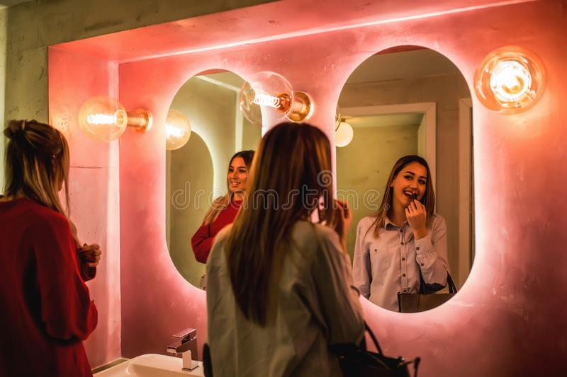 Girl paints lips in the toilet stock photo