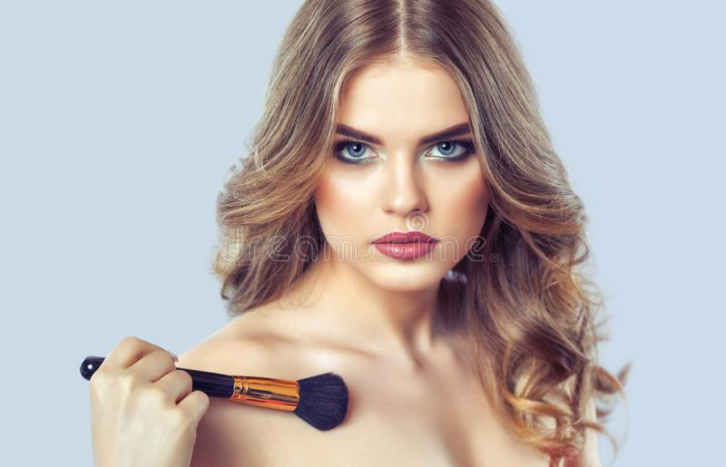 The Girl paints powder on the face and body, completes the smokey eyes make-up in the beauty salon. royalty free stock photography