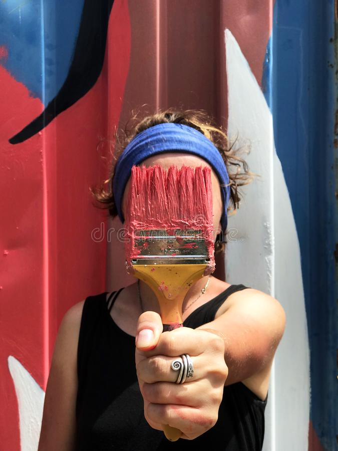Girl paints the wall of the container. Face brush royalty free stock photo