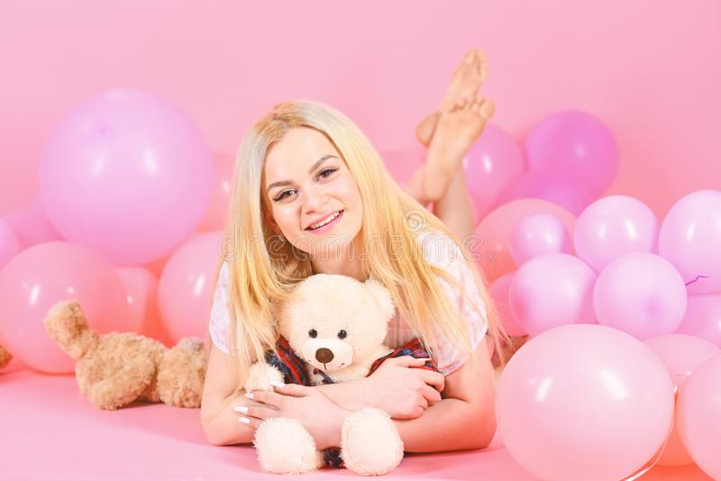 Girl in pajama, domestic clothes lay near air balloons, pink background. Blonde on smiling face relaxing with teddy bear. Toy. Birthday girl concept. Woman cute stock photography