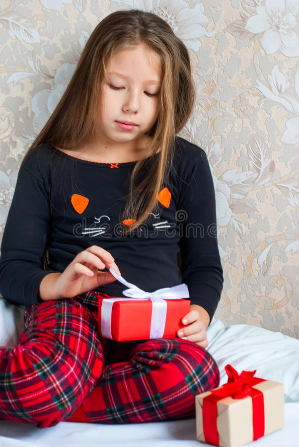 Girl in pajamas with presents boxes on Christmas morning stock image