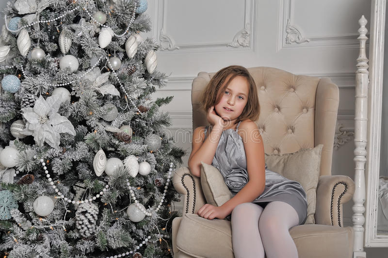 Girl in a pale grey dress sitting in a chair at the Christmas tree stock image