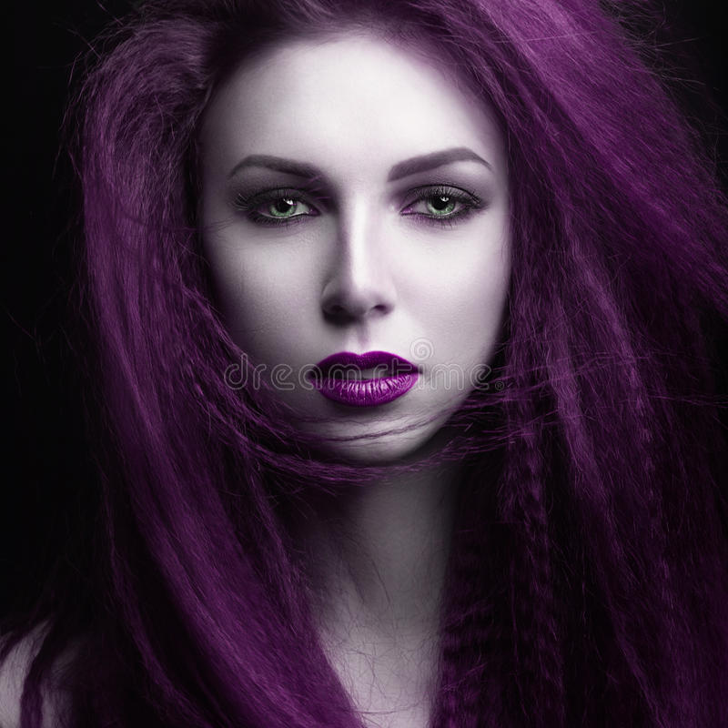 The girl with pale skin and purple hair in the form of a vampire. Insta color. Picture taken in the studio stock photography