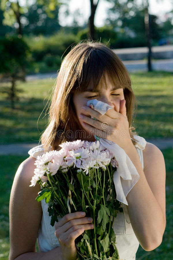 Girl in a park holding some flowers and sneezing stock photo