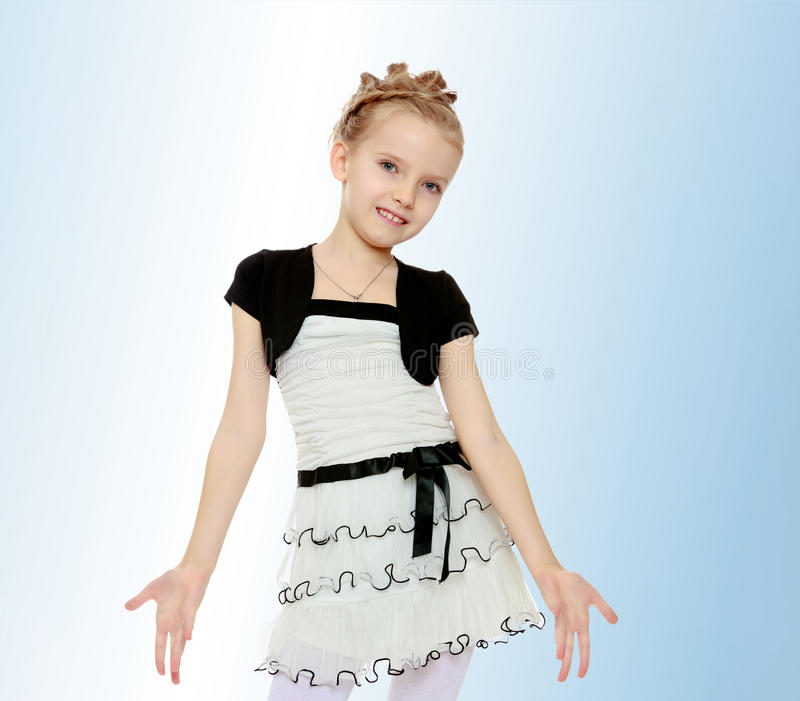 The girl parted in the side of the palm. Beautiful little blonde girl dressed in a white short dress with black sleeves and a black belt.The girl parted in the royalty free stock photography