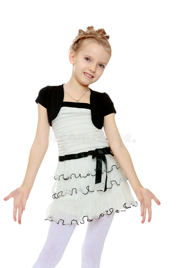 The girl parted in the side of the palm. Beautiful little blonde girl dressed in a white short dress with black sleeves and a black belt.The girl parted in the royalty free stock images